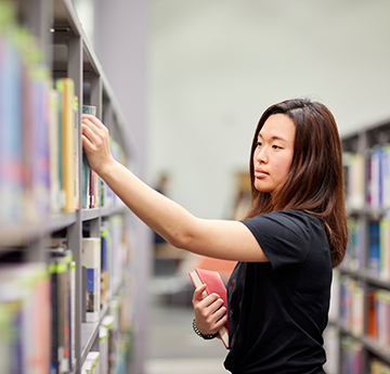 Female student picking a book from the shelf at the library