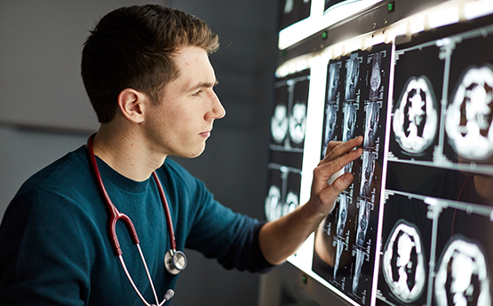 Medical Student examining scan images on a lightboard
